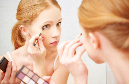young beautiful woman apply makeup eyeshadow front of the mirror photo