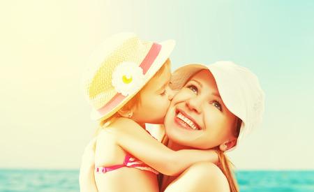 abrazar familia: familia feliz en la playa. hija besa a la madre en el mar