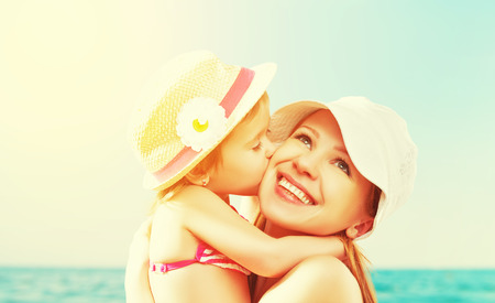 hugs and kisses: happy family on the beach. baby daughter kissing mother  at sea