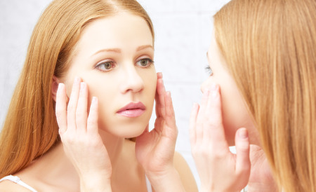 mirror face: young beautiful healthy woman  and the mirror