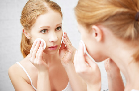 removing: beautiful young woman removes makeup with face skin cotton pad in the mirror Stock Photo