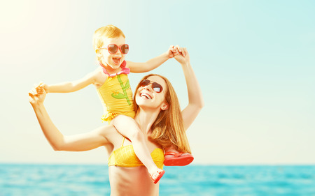 kids playing beach: happy family on the beach. mother and baby daughter  at sea Stock Photo