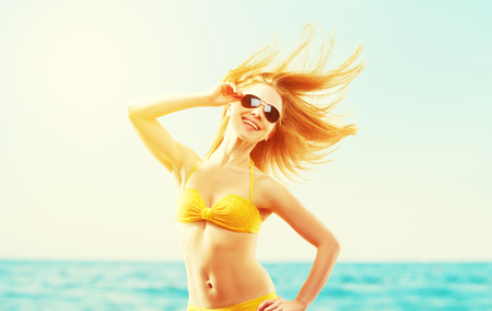hot girl: beautiful young woman with hair flying in the wind and sunglasses summer sea beach