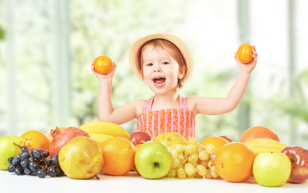 healthy food. happy child girl and a lot of fruit photo