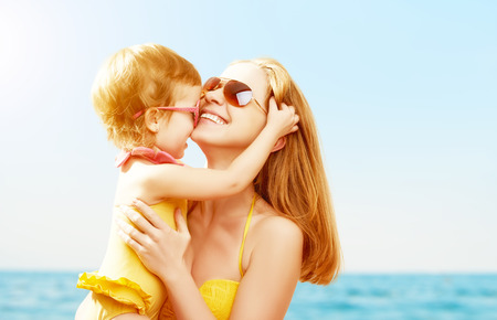 in kiss: happy family on the beach. baby daughter kissing mother  at sea