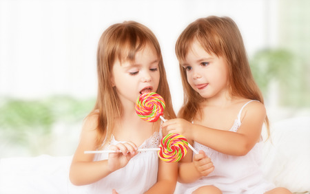 happy girl children twin sisters with lollipops candy