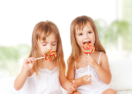 sweet foods: happy girl children twin sisters with lollipops candy