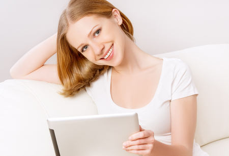 happy woman with tablet pc  on the sofa at home photo