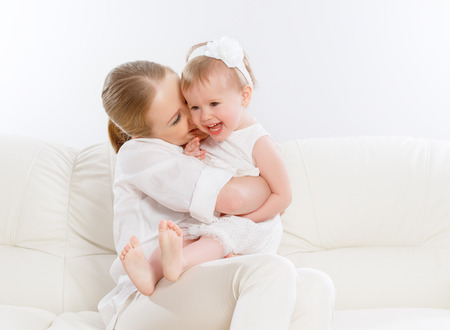 family tickle: happy family. Mother and baby daughter plays at home on the sofa Stock Photo