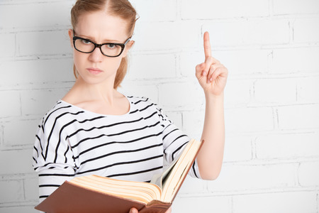 angry strict serious teacher student with book  at a blank white brick wall photo
