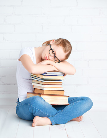 glass brick: tired student girl in glasses asleep hugging books