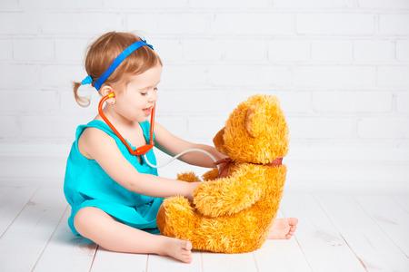 Baby-Mädchen spielen Arzt und behandelt Teddybär Standard-Bild - 38675631