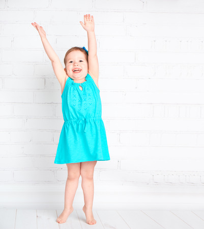 measure height: happy little girl raised her hands up and measure your height, shows that increased Stock Photo