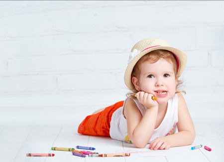 girl drawing: happy dreamy little artist  girl in a hat draws pencil lying on the floor