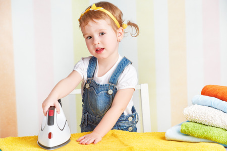 electric iron: cute little baby girl housewife iron clothes iron, is engaged in domestic work