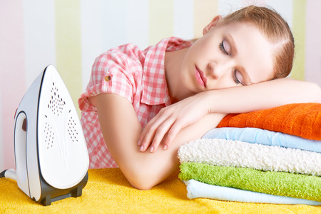 the iron lady: tired housewife fell asleep on the ironing board with iron Stock Photo