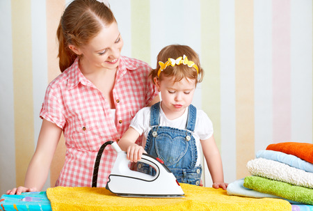 the iron lady: happy family mother and baby daughter together engaged in housework iron clothes iron Stock Photo