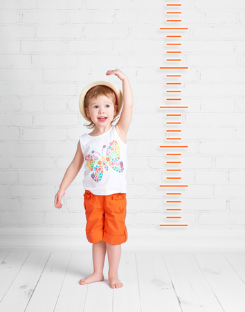 measure height: the happy beautiful baby girl growth measures Stock Photo