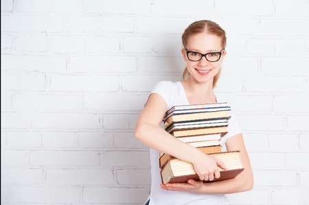 Happy successful student girl with book  at a blank white brick wall photo