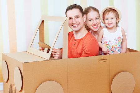 Gelukkige familie moeder, vader, dochter rit op speelgoed auto gemaakt van karton op vakantie Stockfoto