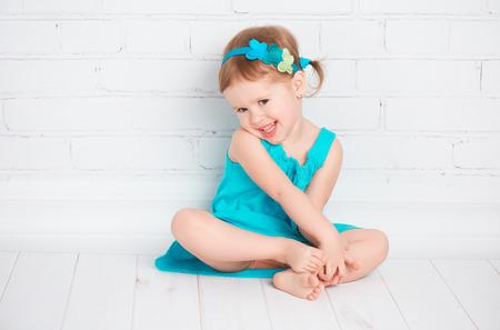mooi klein meisje in een turquoise jurk op de vloer in de buurt van een witte bakstenen muur