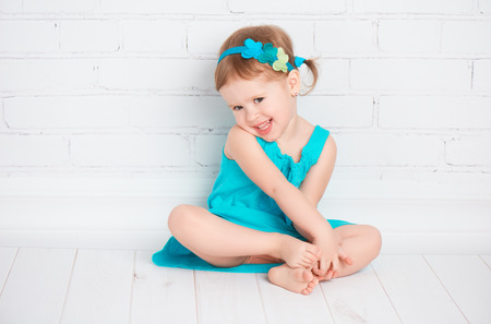 beautiful little baby girl in a turquoise dress on the floor near a white brick wall Standard-Bild