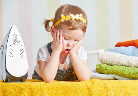 cansado pequeño bebé niña ama de casa ropa de hierro hierro lindo, se dedica al trabajo doméstico