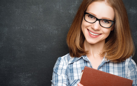 student girl: happy girl student with glasses and a book from the  blackboard