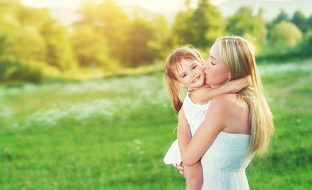 beso: familia feliz en la naturaleza al aire libre madre besando peque�a hija en el prado verde Foto de archivo