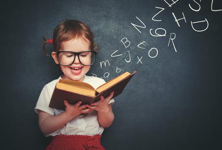 literatura: ni�a linda con gafas de leer un libro con letras saliendo sobre la pizarra Foto de archivo