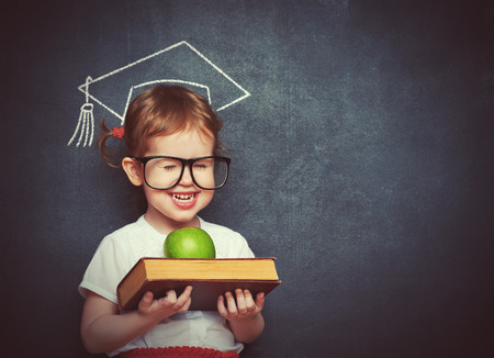 blank chalkboard: pretty little girl schoolgirl with books and apple in a school board Stock Photo