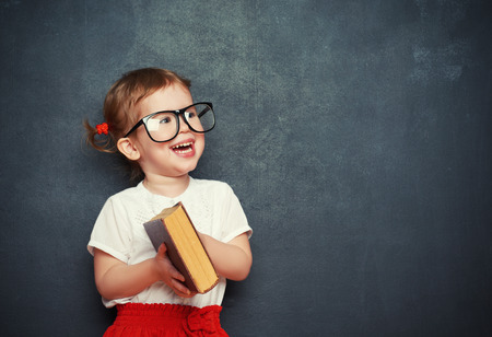 blank chalkboard: happy little girl schoolgirl with a book from the blackboard Stock Photo