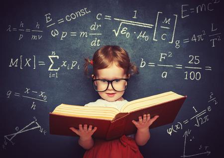 niños en la escuela: colegiala niño prodigio niña con un libro de la pizarra con fórmulas físicas Foto de archivo