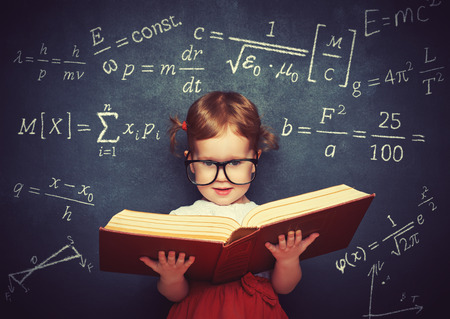 girl: wunderkind little girl schoolgirl with a book from the blackboard with physical formulas