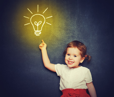 smart girl: concept, the idea of a happy little girl with a bulb at the blackboard Stock Photo
