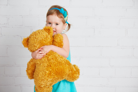 in loved: little girl baby hugging a loved teddy bear Stock Photo