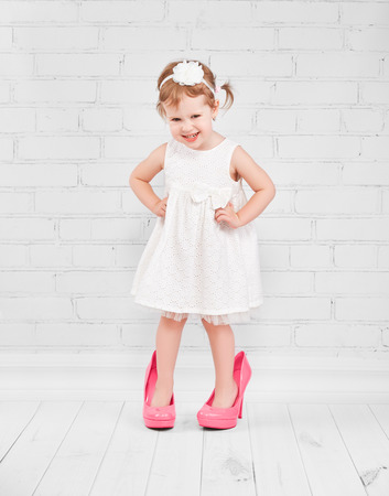 little girl fashionista in her mother's big pink heeled shoes