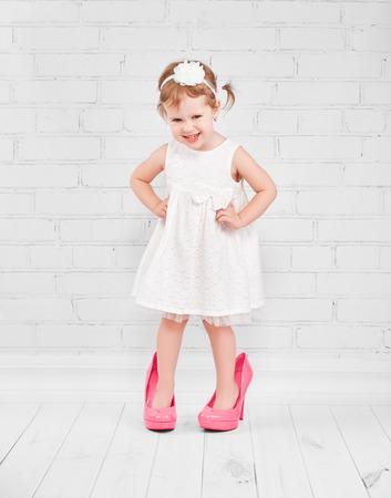 pequeño: pequeña fashionista niña en grandes rosados ??de tacón zapatos de su madre Foto de archivo