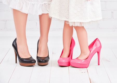 woman red dress: legs mother and daughter little girl fashionista in pink shoes on high heels