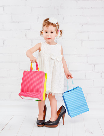 big and small: funny little girl fashionista in big lady heeled shoes went on shopping