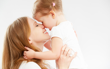 kid's day: happy family mother and child baby daughter hugging and kissing