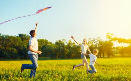 夏の自然の中の幸せな家族。父、母、息子の子が凧の飛行