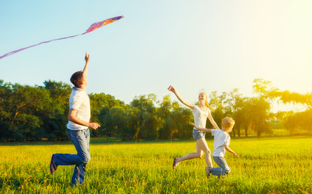 family on grass: happy family in summer nature. Dad, mom and son child flying a kite