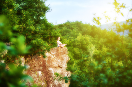 pureness: woman meditating in lotus posture, doing yoga on top of the mountain on a rock in nature in the forest