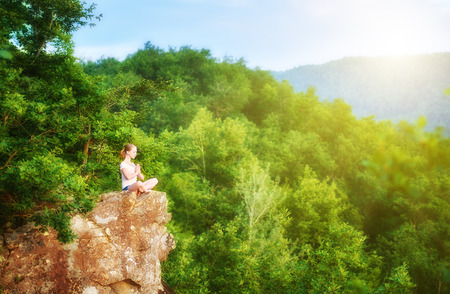mujer meditando: Mujer meditando en la postura de loto, hacer yoga en la cima de la montaña en una roca en la naturaleza en el bosque