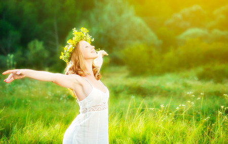 enjoying life: happy woman in wreath outdoors summer enjoying life opening hands