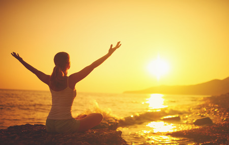 здравоохранение: йога на закате на пляже. женщина делает йогу, выполняя асаны и наслаждаться жизнью на берегу моря