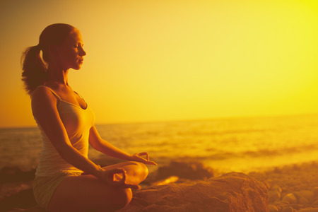 yoga meditation: yoga in the beach. woman meditating in lotus pose on the beach at sunset