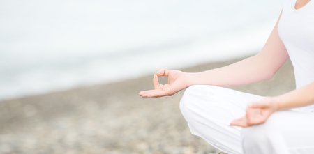 gyan: hand of a woman meditating in a yoga pose on the beach