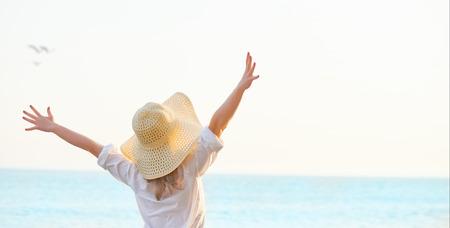 Gelukkige vrouw die zich uitgestrekte armen achterover en geniet van het leven op het strand op zee Stockfoto